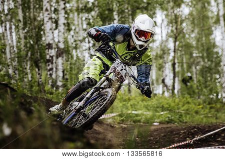 Miass Russia - May 29 2016: closeup man athlete mountain biking around sharp turn in forest during Cup