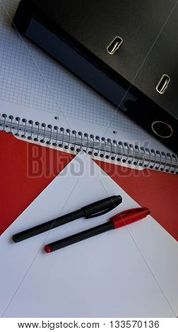 two pencils lie on white paper, the red folder and the black folder, the black folder big, a pencil black, a pencil red nearby,