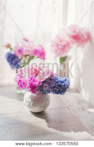 on a table in the sun vase with a bouquet of pink peonies and hyacinths