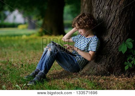 The boy of 8-9 years with enthusiasm is engaged with the tablet. The child in earphones with interest looks at the screen. The boy sits in park having leaned against a trunk of an old tree.