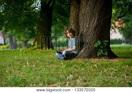 The boy with the tablet on a lap. He sits in park under a big old tree. In ears earphones. Thoughtful face. The boy looks in a camera.