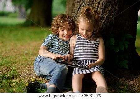 The brother and the sister of 8-9 years play with passion on the tablet. They sit having leaned against a trunk of a big tree. On a lap tablet. In ears one earphones for two.