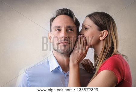 Woman whispering into a man's ear