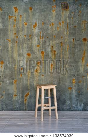 Bar stool chair on concrete wall with rust spots