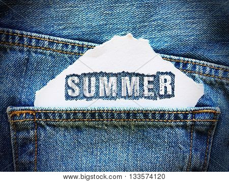 summer word on white paper in the pocket of blue denim jeans
