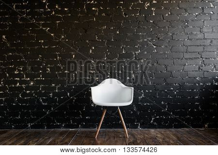 White chair standing in room on brown wooden floor over black brick wall.