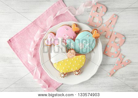 Letters of word baby and spice cake on wooden background