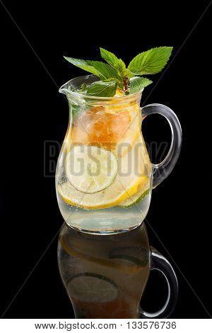Lemonade Pitcher With Lemon Orange Lime And Mint Over Black Background