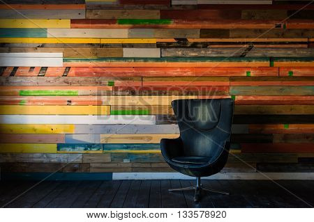 Modern egg chair on a colorful wooden wall.