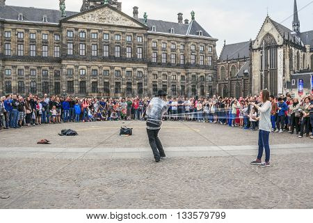AMSTERDAM, NETHERLANDS - MAY 7, 2013: This is evening performance of amateur actors on Dam Square for tourists and residents.