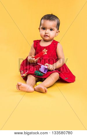 indian baby girl playing with toys or blocks or soft toys over yellow background, asian infant playing with toys, indian toddler playing indoor