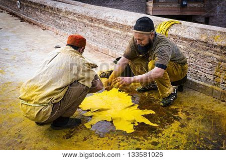 Fez Morocco - April 11 2016: Two man working in a tannery in the city of Fez in Morocco.
