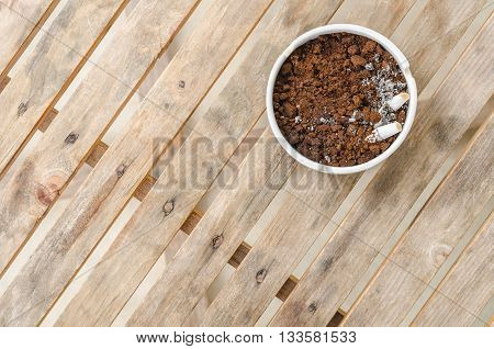 The ceramic ashtray contain coffee ground on wood table for protection fire from cigarette.