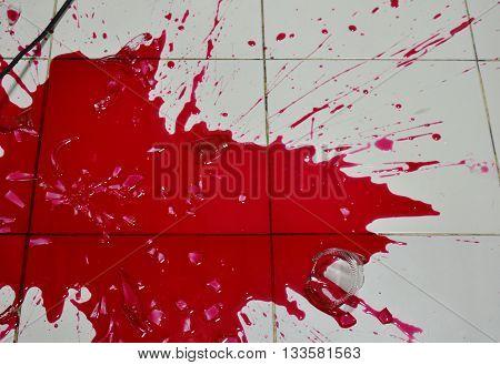 red liquid splash on house tile floor