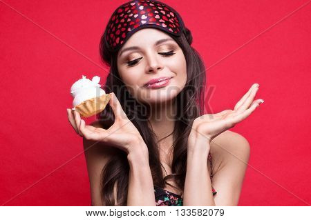 Funny young woman in sleeping mask and pajamas sweets in the hands on a red background. The beauty of the face. Photos shot in studio
