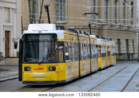 BERLIN - DECEMBER 26: Yellow tram in city street on December 26 2014 in Berlin Germany. The tram in Berlin is one of the oldest tram systems in the world.