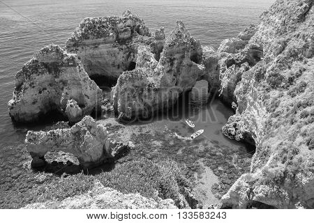 Ponta da Piedade - unique rock formation in the ocean - two boats with tourists visiting famous grottoes. Number one attraction in Lagos, Algrave, Portugal. Black and white