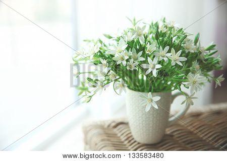 Bouquet of little white flowers on wicker furniture