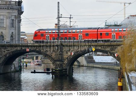 BERLIN - DECEMBER 26: Red train on the bridge on 26 December 2013 in Berlin, Germany. Deutsche Bahn (state-owned private company) is the main provider of railway service
