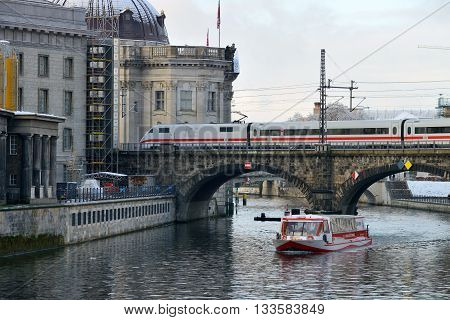 BERLIN - DECEMBER 26: Train on the bridge on 26 December 2013 in Berlin Germany. Deutsche Bahn (state-owned private company) is the main provider of railway service