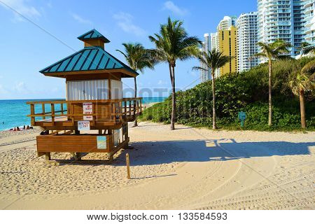 Lifeguard station on a sandy beach with Palm Trees and highrise buildings overlooking the Atlantic Ocean taken at Sunny Isles Beach in Miami Dade, FL