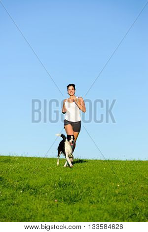 Fit woman and dog running and exercising outdoor over grass field on summer or spring. Happy female athlete training and exercising with her pet.