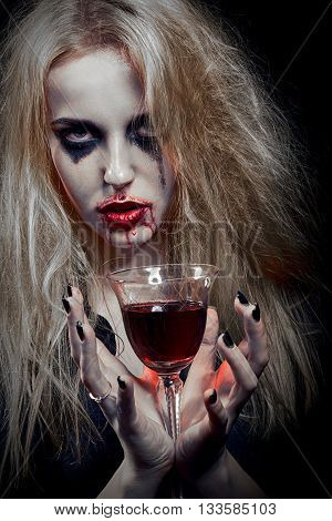 blond witch with bloody glass on black background toned image