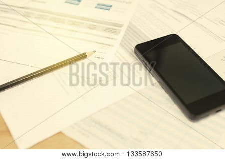 Bill and smart phone with pencil Bill for income and expenditure and tax Selective focus Vintage style