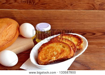 Home fried bread croutons. Fried bread with egg breakfast. Simple make roasted bread. Quick appetizer recipe. Ingredients for cooking breakfast. Wooden background with empty space for text
