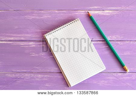 Blank notepad and pencil on wooden board. Open notebook with a spring. Page notebook in cage. Empty paper sheet. Single pen. Stationery on a table. Lilac wooden background