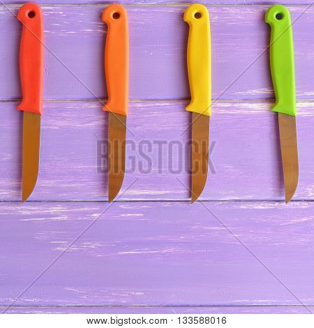 A set of kitchen knives with bright handles. Fixed-blade knives handles. Useful kitchen tools. Kitchen knives used in food preparation. Lavender wooden background. Top view