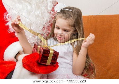 Girl Unleashes A Red Ribbon Gift In The Hands Of Santa Claus