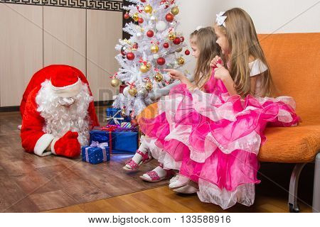 Two Girls Saw That Santa Claus Puts Presents Under The Christmas Tree