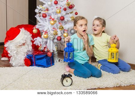 Two Girls With Flashlights Dreaming Of Gifts On New Years Night, And Santa Claus Put Presents Under