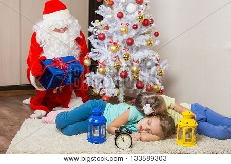 Santa Claus In New Years Eve Gifts Lays Out And Looked At The Fallen Asleep In Front Of Christmas Tr