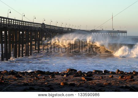 Ocean waves throughout at storm crashing into a the Ventura pier.