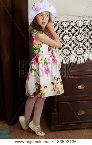 Adorable little girl in fine white dress with large red roses leaned a hand on the old grandmother's dresser. Retro style
