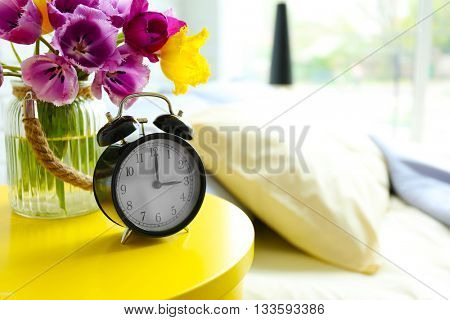 Alarm clock and flower bouquet on a side table by the bed