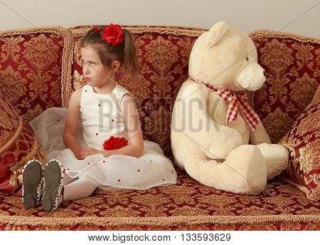 Adorable little girl in fancy white dress sitting on the couch, offended by a big white Teddy bear