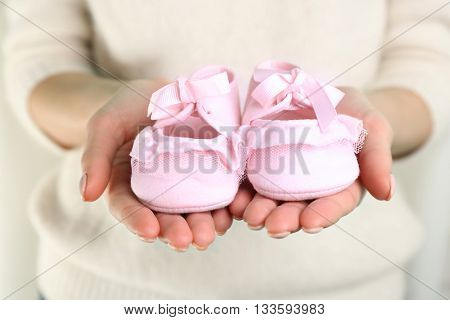 Woman holding baby booties, closeup