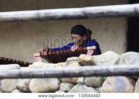 Hainan China - April 7 2012: Mature woman works on an ancient loom in Hainan. China