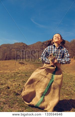 Little girl jumps with a lot of potatoes outdoors