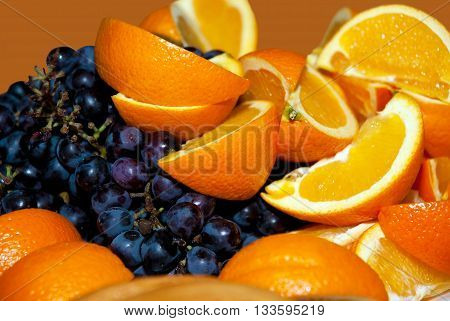 Slices of oranges and grapes closeup. Juicy fresh fruit on a platter. Useful vitamin food for diet. The gifts of nature for people. Tropical and southern fruit blend.