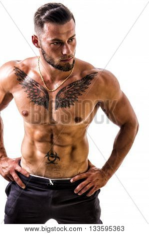 Handsome shirtless muscular man with elegant pants, standing, isolated on white background