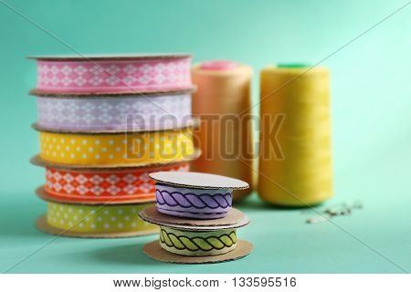 Spools of color ribbons on turquoise background
