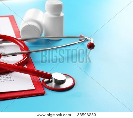 Red stethoscope and pills on blue background