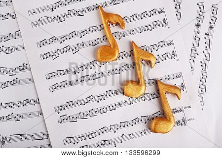 Golden music notes on music sheets background