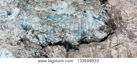 A blue white dirty glacier melts on top of a brown colored stone.