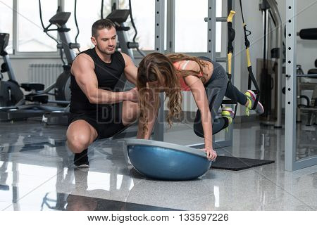 Personal Trainer Helping Woman On Trx Fitness Straps