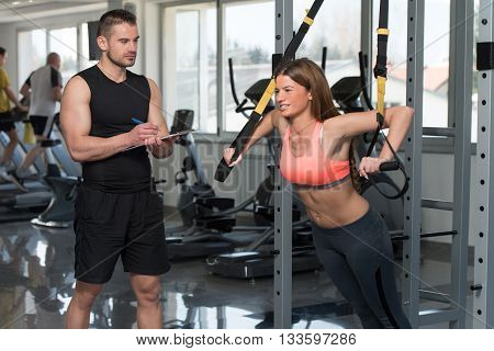 Trainer With Clipboard Woman On Trx Fitness Straps